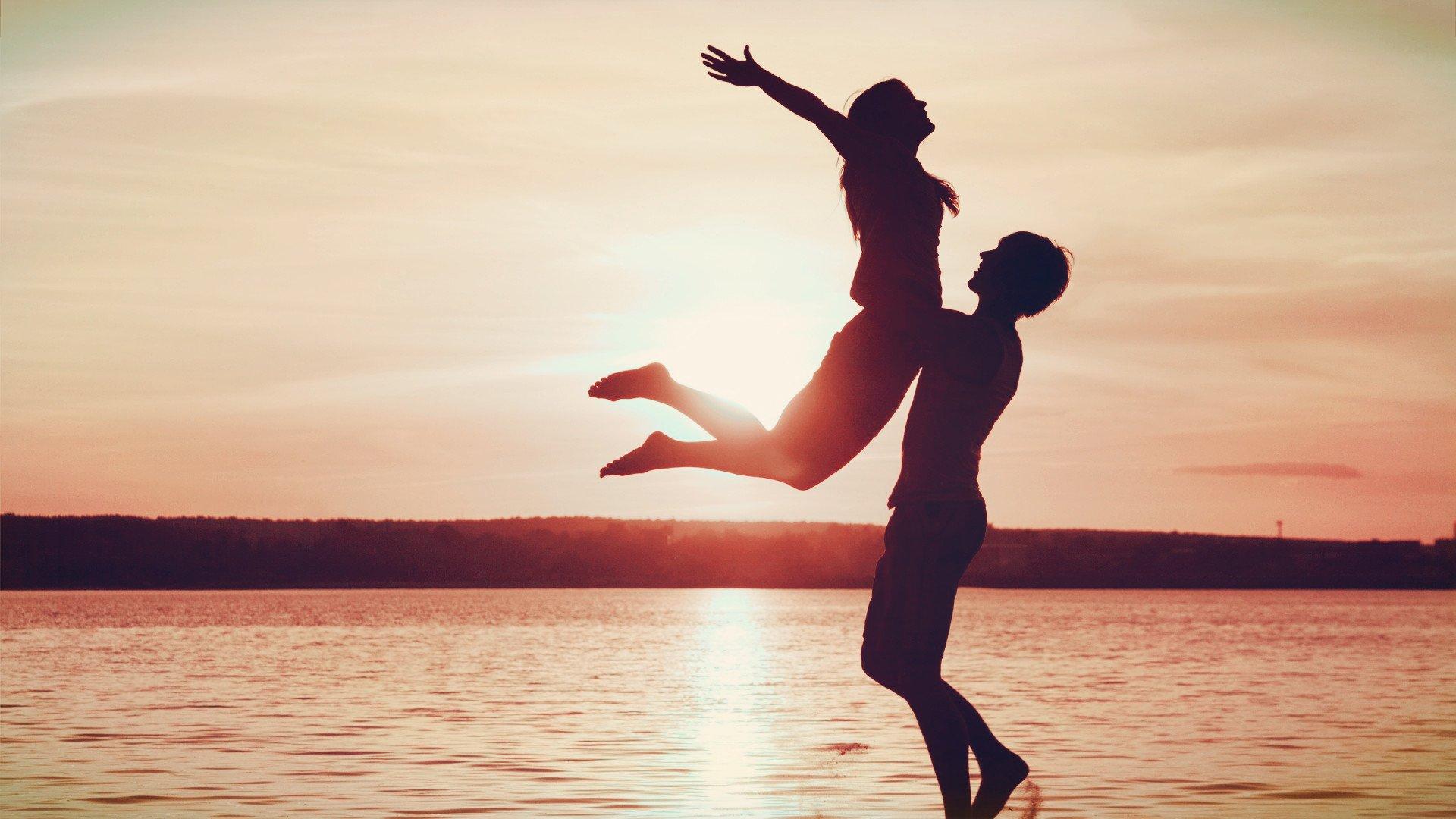 精选夕阳中海边拥抱的情侣甜蜜浪漫ppt背景图片下载
