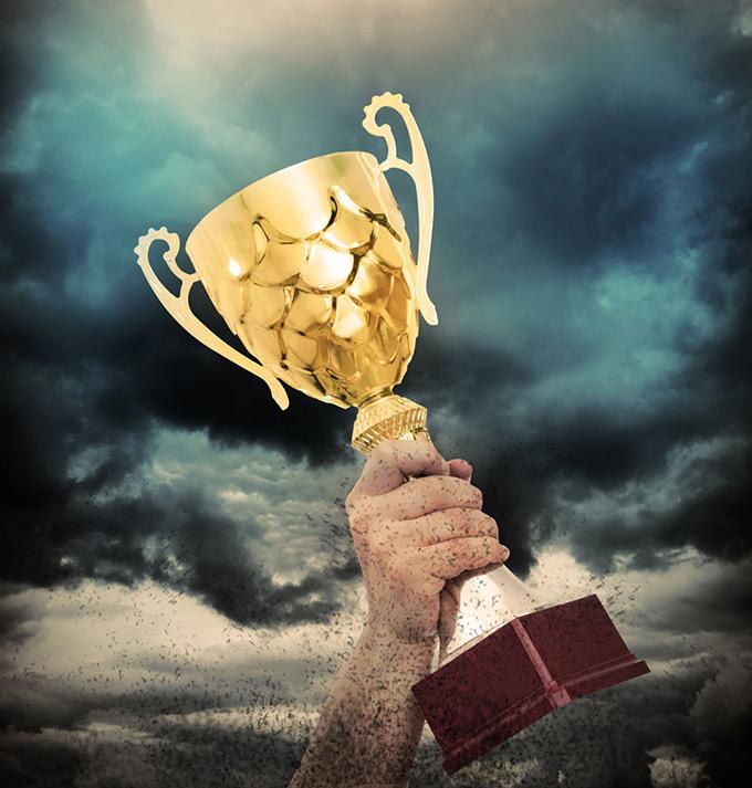 阴霾下举着奖杯的手ppt背景图片下载